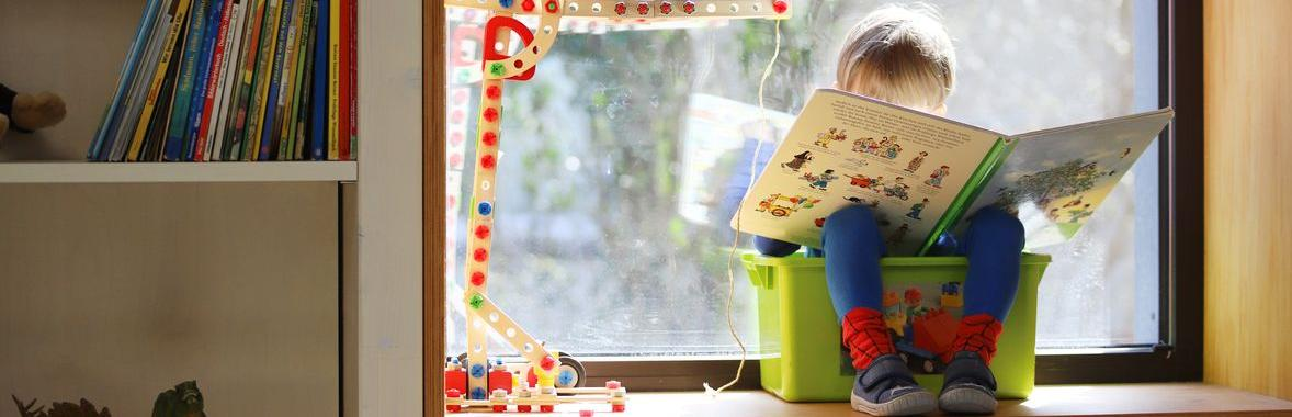 Child reading on windowsill