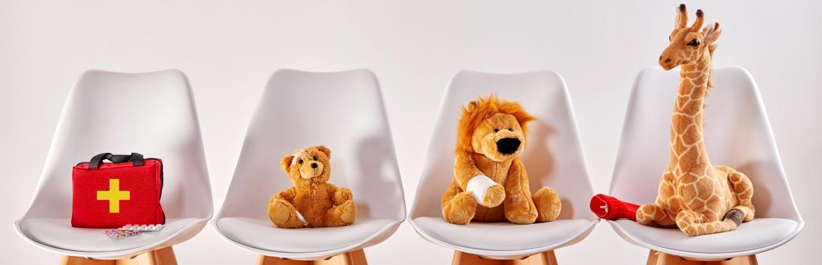 teddies sat on chairs with bandaged arms
