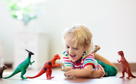 Child lying down on floor lining up dinosaurs