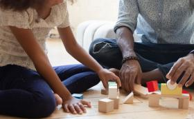 Dad and two children sat on floor stacking blocks
