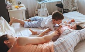 parent lying with children playing